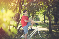Young man on bike in wood with bottle of water resting Royalty Free Stock Photo