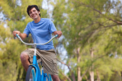 Young Man on bike wth trees Stock Photos