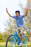 Young Man on bike wth trees Royalty Free Stock Photography