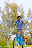 Young Man on bike wth trees Stock Images
