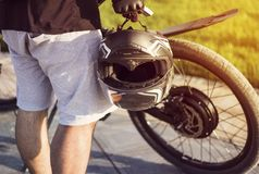 Young man biker with protective helmet in hand standing near electric bike. Ebike bicycle environmentally friendly eco e-mountainbike transport. Healthy royalty free stock images
