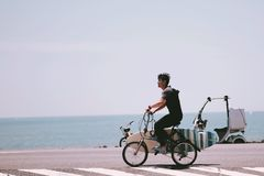 A young man biking to surf at the sea royalty free stock image