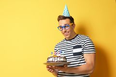 Young man with birthday cake on color background Stock Photography