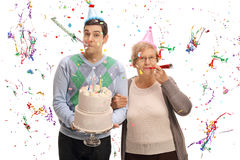 Young man with birthday cake and mature woman blowing party horn Stock Photo