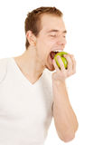 Young man bites green fresh apple royalty free stock photography