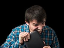 The young man bites his electronic tablet with anger. royalty free stock photography