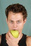Young man biting an apple Royalty Free Stock Photos