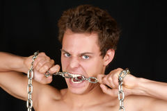 Young man biting a chain Royalty Free Stock Photography