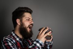 Man biting black hamburger. Young man biting fresh tasty black hamburger stock photo