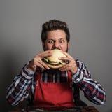 Man biting black hamburger. Young man biting fresh tasty hamburger royalty free stock photography