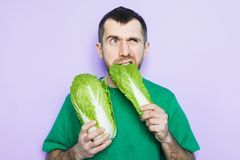 Young man biting on a leaf of Beijing napa cabbage. Doubt face expression. Light purple background royalty free stock image