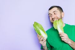 Young man biting on a leaf of Beijing napa cabbage. Enjoyment face expression. Light purple background, copy space royalty free stock photography