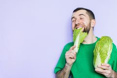 Young man biting on a leaf of Beijing napa cabbage. Enjoyment face expression. Light purple background, copy space royalty free stock photos