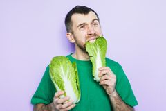 Young man biting on a leaf of Beijing napa cabbage. Young bearded man biting on a leaf of Beijing napa cabbage, doubt face expression. Light purple background stock image