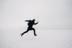 A young man in a black backpack and traveling on the frozen pond. Young guy hipster in black and with a backpack running on the frozen pond Royalty Free Stock Photography