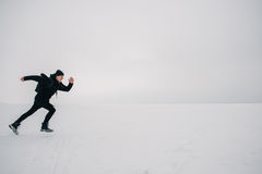 A young man in a black backpack and traveling on the frozen pond. Young guy hipster in black and with a backpack running on the frozen pond Stock Photo