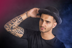 Young man with black bowler hat and tattoos Stock Photography