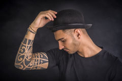 Young man with black bowler hat and tattoos Royalty Free Stock Photography