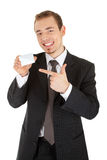 Young man in a black business suit and card in his Royalty Free Stock Photos