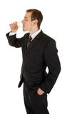 Young man in a black business suit holds a glass o Stock Photo
