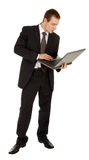 Young man in a black business suit with a laptop Stock Photography