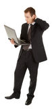 Young man in a black business suit with a laptop Stock Photos