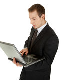 Young man in a black business suit with a laptop Royalty Free Stock Image