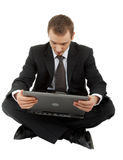 Young man in a black business suit with a laptop Stock Images