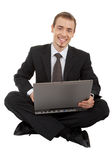 Young man in a black business suit with a laptop Royalty Free Stock Images