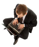 Young man in a black business suit with a laptop Stock Image