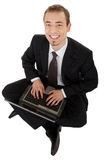Young man in a black business suit with a laptop Royalty Free Stock Photography