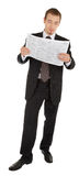 Young man in a black business suit reads the newsp Royalty Free Stock Images