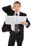 Young man in a black business suit reads the newsp Royalty Free Stock Photography