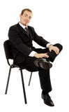 Young man in a black business suit sitting on a ch Royalty Free Stock Images
