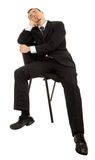 Young man in a black business suit sitting on a ch Stock Photography