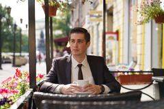 A young man in a black business suit, white shirt and tie is sitting in a city street cafe at a table and enjoying a Cup of coffee royalty free stock image