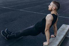 A young man in black clothes is exercising outdoors close up. fitness athlete on the sports field. training with projectiles. warm stock images