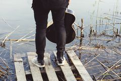 A young man in black clothes with a guitar in his hand is standing on a dilapidated bridge on the river bank royalty free stock image