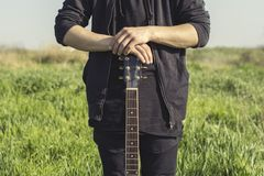 A young man in black clothes is holding a guitar with both hands against the blue sky and green grass royalty free stock image