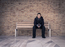 Young man(in black clothes) sitting on a bench and looking directly forward. Has joined hands with fingers touching. In the background is a brick wall and in Royalty Free Stock Photography