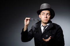 The young man in black coat and hat against gray Stock Photo