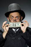 Young man in black coat holding money against gray Stock Images