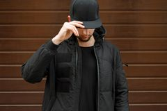 Young man in a black fashionable baseball cap. And a winter warm jacket posing on the street royalty free stock images