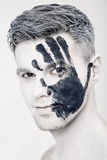 Young man with black hand print on white face. Closeup Portrait. Professional Fashion Makeup. fantasy art makeup Royalty Free Stock Photography