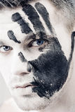 Young man with black hand print on white face. Closeup Portrait.  Professional Fashion Makeup. fantasy art  makeup. Young man with black hand print on his white Royalty Free Stock Photos