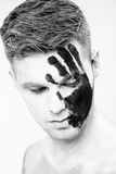 Young man with black hand print on white face. Closeup Portrait.  Professional Fashion Makeup. fantasy art  makeup. Young man with black hand print on his white Royalty Free Stock Photography