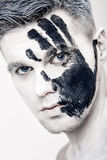 Young man with black hand print on white face. Closeup Portrait.  Professional Fashion Makeup. fantasy art  makeup. Young man with black hand print on his white Stock Photo