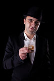 Young man with a black hat and a glass of whiskey Stock Photo