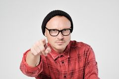 A young man in black hat and glasses like hipster looks at the camera in displeasure. He strechs hand ahead. Stock Image
