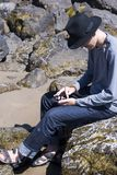 Young man in black hat checks messages in social networks on the ocean shore. Young man in black hat with moss and checking messages in social networks and Royalty Free Stock Photography